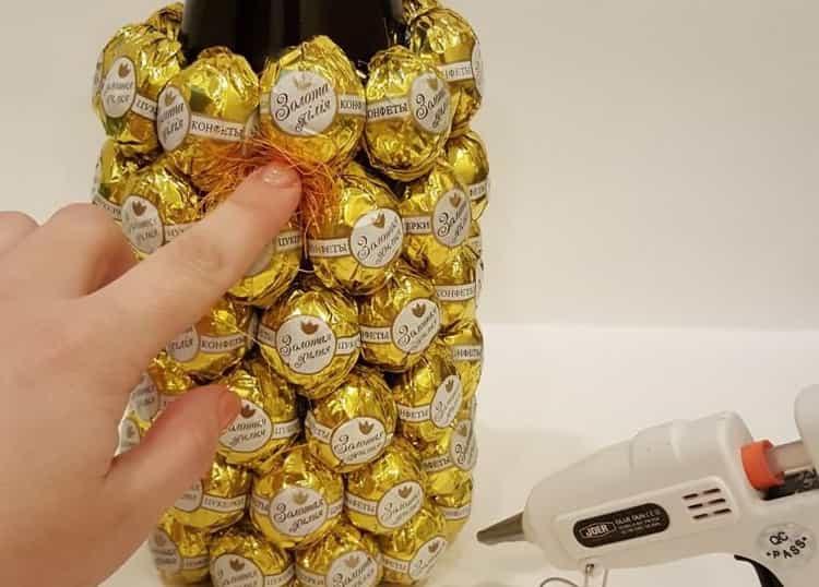 Наклейте все конфеты на бутылку